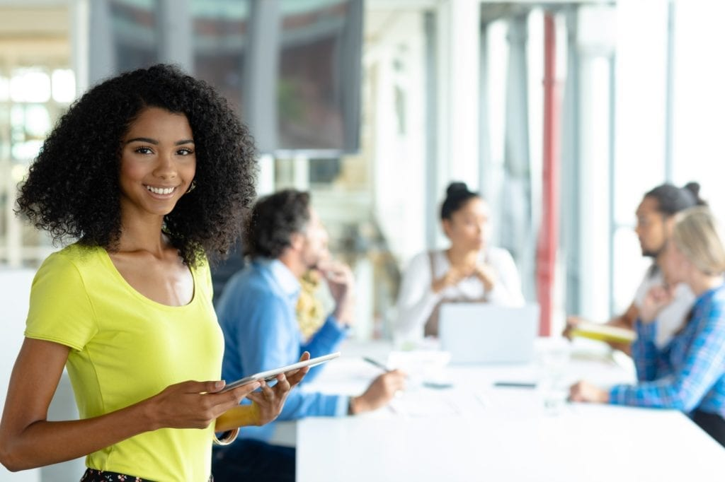 Young African-american businesswoman with digital tablet looking at camera