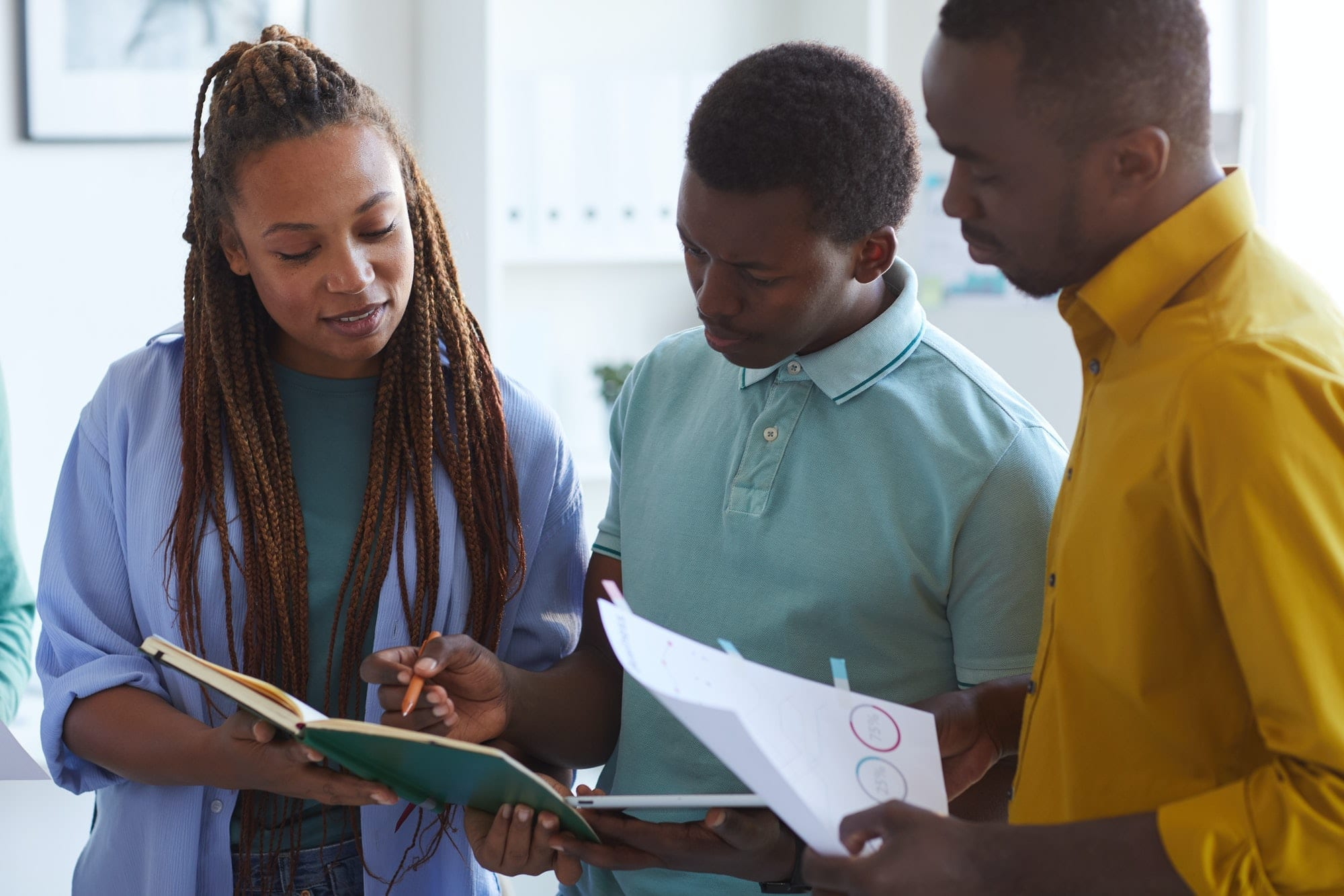 African-American Business Team Discussing Documents in Office