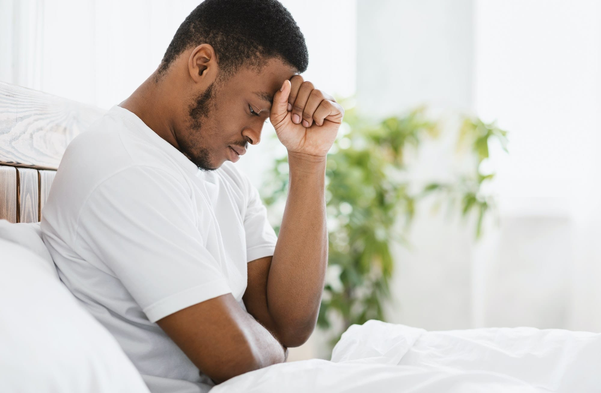 African American Man Suffering Depression Sitting In Bed At Home