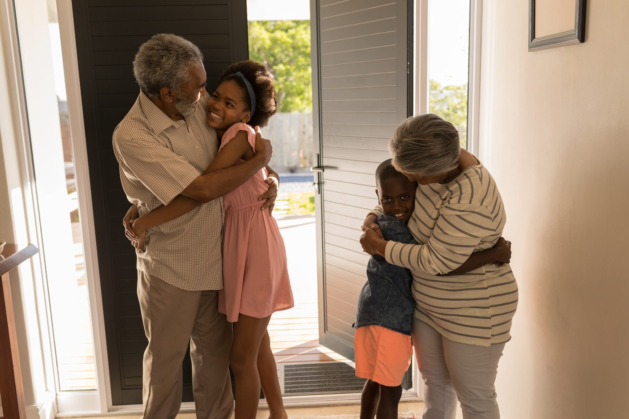 Front view of happy African American grandparents hugging their grandchildren at home