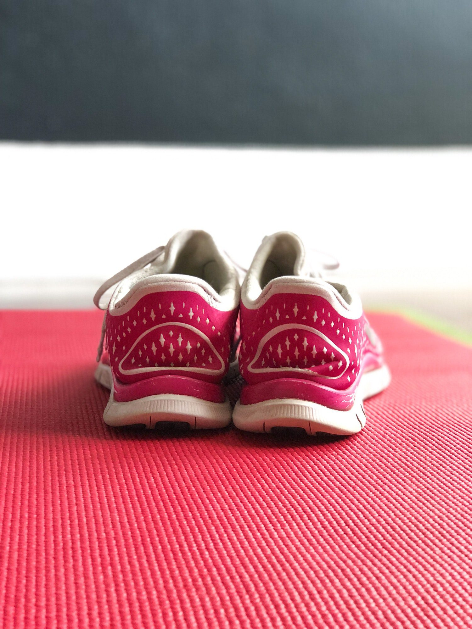 A pair of pink tennis shoes resting on a yoga mat at a gym.